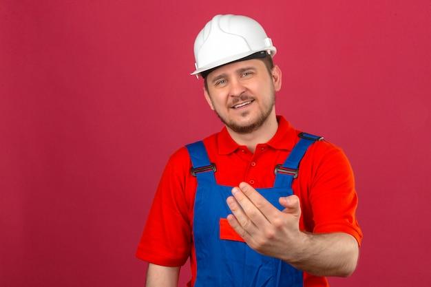 Bouwersmens die eenvormige bouw dragen en veiligheidshelm die glimlachend een gebaar met hand maken die over geïsoleerde roze muur uitnodigen te komen