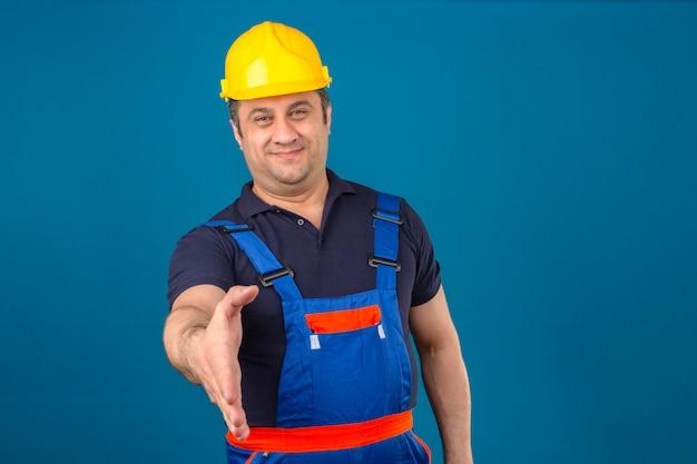 Bouwersmens die eenvormige bouw dragen en veiligheidshelm die hand aanbieden om groet te begroeten en gebaar over geïsoleerde blauwe muur welkom te heten