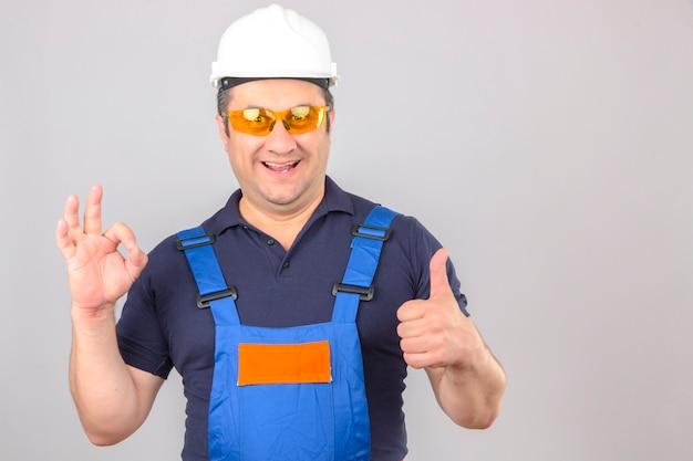 Bouwersmens die eenvormige bouw dragen en veiligheidshelm die ok teken maken en duimen met glimlach op gezicht over geïsoleerde witte muur tonen