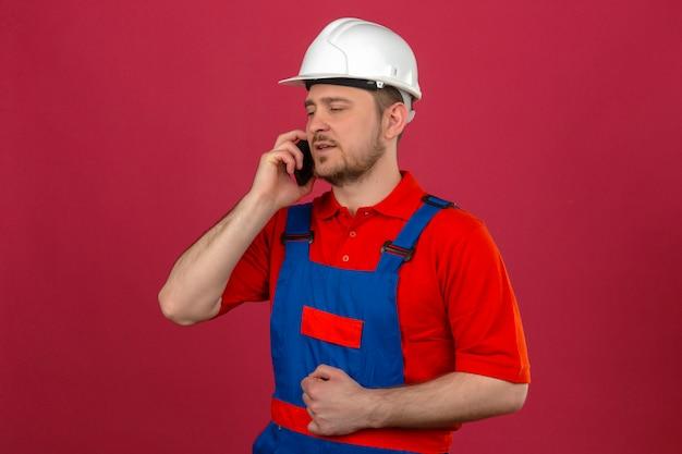 Bouwersmens die eenvormige bouw dragen en veiligheidshelm die op mobiele telefoon met ernstig gezicht over geïsoleerde roze muur spreken