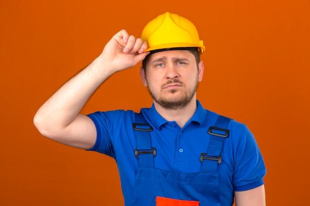Bouwersmens die eenvormige bouw dragen en veiligheidshelm die vermoeid en overwerkt wat betreft helm die zich over geïsoleerde oranje muur bevinden bevinden zich