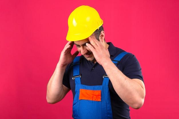 Bouwersmens die eenvormige bouw dragen en veiligheidshelm die vermoeid en overwerkt wat betreft hoofd het voelen hoofdpijn die zich over geïsoleerde roze muur bevinden