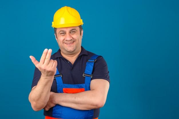 Bouwersmens die eenvormige bouw en veiligheidshelm dragen die vraaggebaar met hand en vingers over geïsoleerde blauwe muur maken