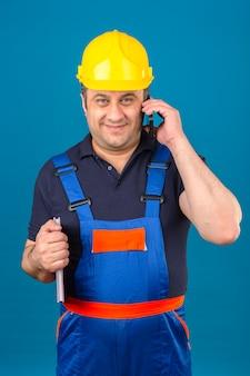 Bouwersmens die eenvormige bouw en veiligheidshelm met glimlach op gezicht dragen en op mobiele telefoon over geïsoleerde blauwe muur spreken