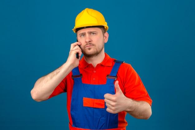 Bouwersmens eenvormige bouw dragen en veiligheidshelm die op mobiele telefoon spreken met ernstig gezicht die duim tonen die over geïsoleerde blauwe muur opstaan