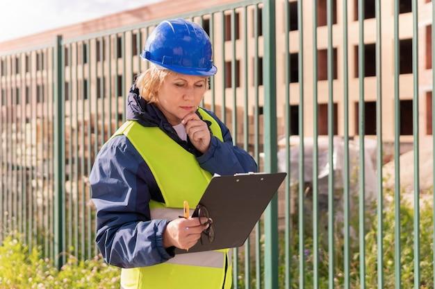 Bouwersvrouw bij bouwwerf in een groen vest en een helm met een tablet