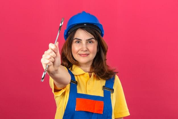 Bouwersvrouw die eenvormige bouw dragen en de moersleutel die van de veiligheidshelm glimlachen het uitrekken zich uit moersleutel bevinden die zich over geïsoleerde roze muur bevinden