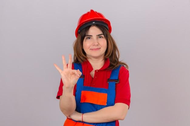 Bouwersvrouw die eenvormige bouw dragen en veiligheidshelm die het vriendschappelijke tonen glimlachen en met vingers nummer drie over geïsoleerde witte muur glimlachen