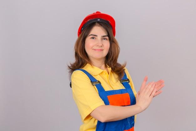 Bouwersvrouw die eenvormige bouw dragen en veiligheidshelm die na presentatie toejuichen die over geïsoleerde witte muur glimlachen