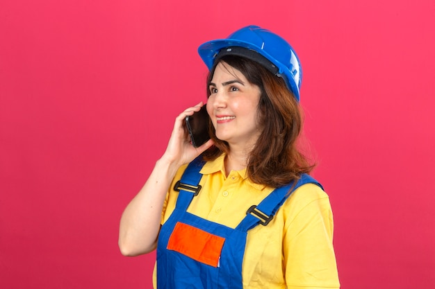 Bouwersvrouw eenvormige bouw dragen en veiligheidshelm die bij het mobiele telefoon glimlachen vrolijk over geïsoleerde roze muur spreken