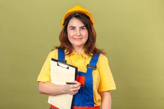 Bouwersvrouw in eenvormige bouw en de holdingsklembord en pen die van de veiligheidshelm zeker met glimlach op gezicht over geïsoleerde groene muur kijken