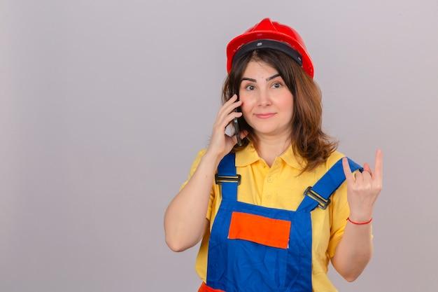 Bouwersvrouw in eenvormige bouw en veiligheidshelm die op mobiele telefoon spreken die rotssymbool met vingers over geïsoleerde witte muur doen