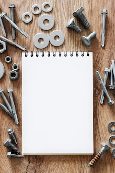 Bouwgereedschap. de schroeven, moeren en bouten gerangschikt rond het lege spiraalgebonden document van het notaboek op houten achtergrond. reparatie, huisverbetering concept. vrije ruimte voor tekst, bovenaanzicht, plat leggen.