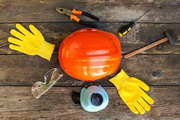 Bouwgereedschap en beschermingsmiddelen op een oude houten tafel. bovenaanzicht. plat leggen.
