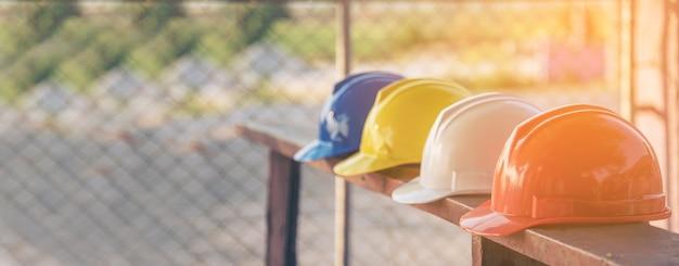 Bouwhelm veiligheidsgereedschap apparatuur voor werknemers op de bouwplaats voor technische bescherming hoofdnorm. veel bouwvakkerhelm op rij met exemplaarruimte. engineering bouwconcept