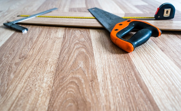 Bouwhulpmiddelen die op houten vloerplanken liggen voor werk. abstracte renovatie en wederopbouw achtergrond met selectieve aandacht en kopie ruimte