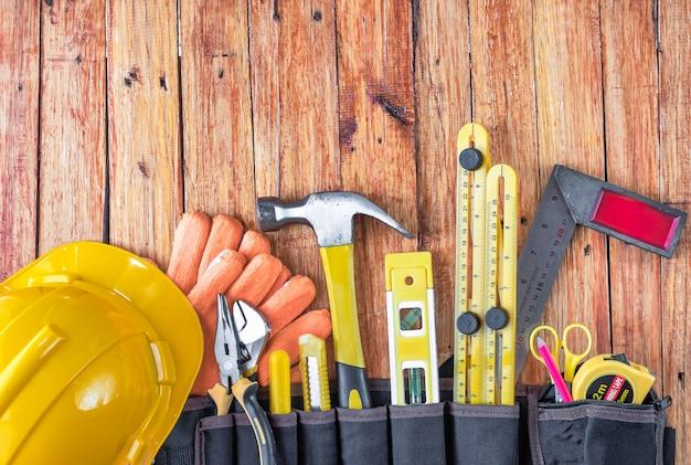 Bouwhulpmiddelen in toolbelt op houten achtergrond