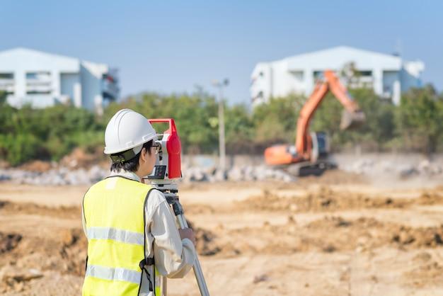 Bouwingenieur gebruiken landmeter-apparatuur die bouwwerf controleren