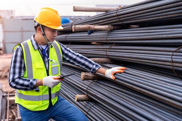 Bouwingenieur of werknemer gebruiken een tablet die de kwaliteit van staal op de bouwplaats controleert.