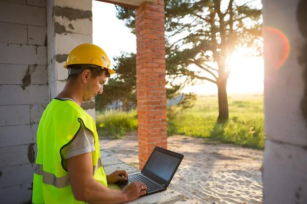 Bouwingenieur op de bouwplaats van een huis werkt op een computer