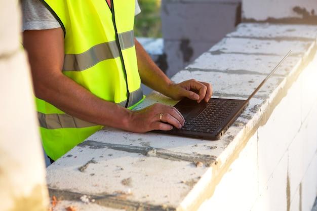 Bouwingenieur op de bouwplaats werkt op een computer in een reflecterend vest