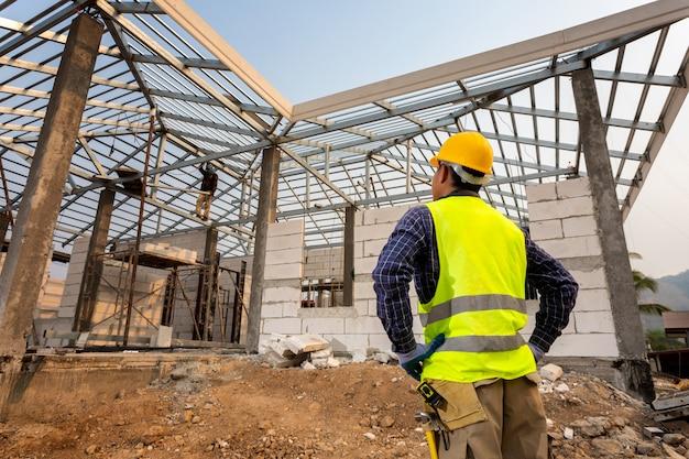 Bouwingenieurarbeider, civiel-ingenieur die het werk controleren bij de bouwwerf, het concept van de huisbouw.