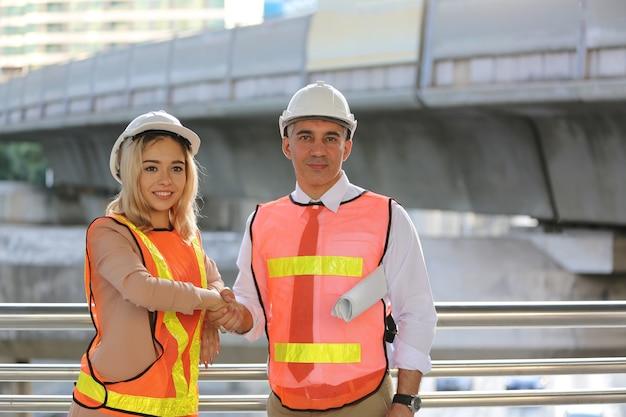 Bouwingenieurs doen handdruk na controle van nieuw project op een bouwplaats