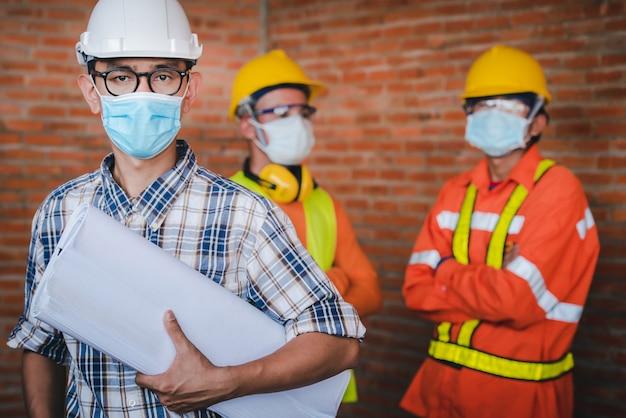 Bouwingenieurs en drie architecten dragen medische maskers om coronaire infecties te voorkomen. covid-19 - supervisor en volgeling met maskers staan in het bouwgebied.