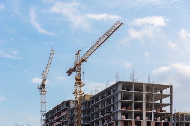 Bouwkraan aangelegd op een achtergrond van blauwe lucht bouwmachines bouwt een huis