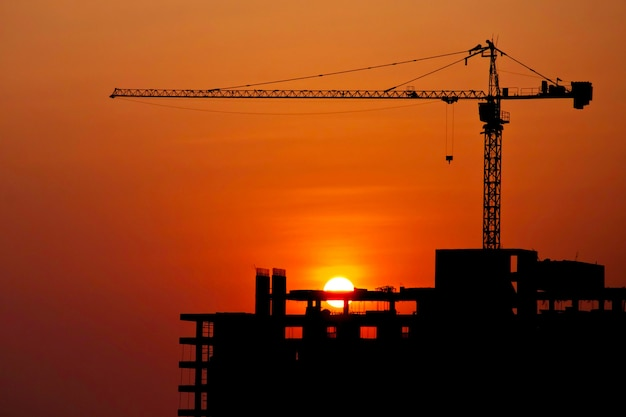 Bouwkraan bij bouwwerf met zonsondergangmilieu