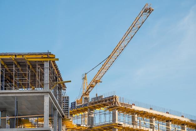 Bouwkraan dichtbij nieuw gebouwd huis. bouw en ontwikkeling van horizontale foto