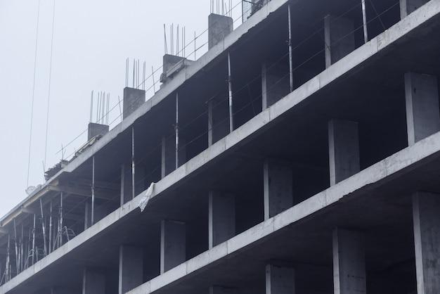 Bouwkraan in mistig weer bij de bouw van woningbouw.