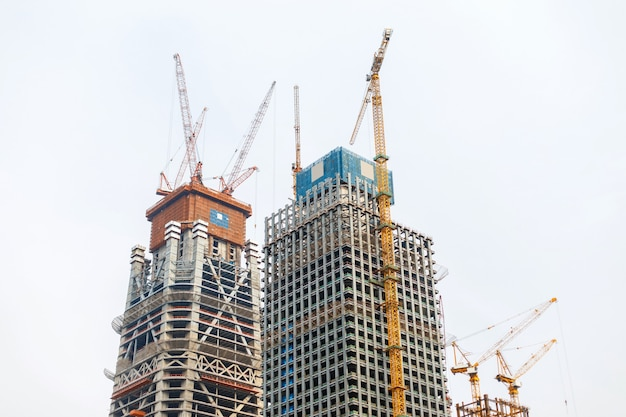 Bouwkranen die moderne wolkenkrabber bouwen