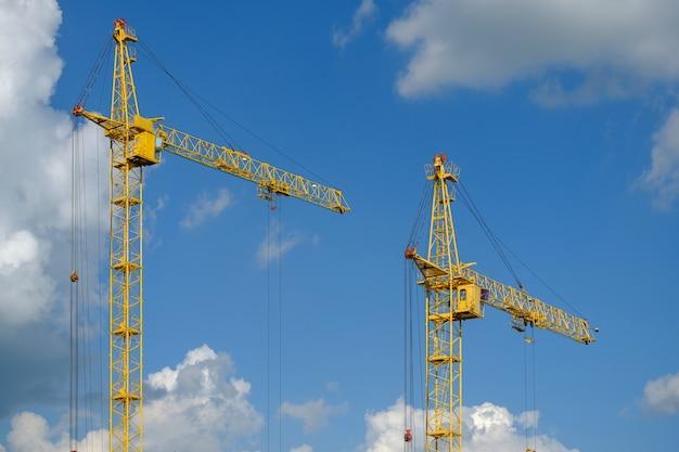 Bouwkranen en het bouwen van huis tegen de blauwe hemel