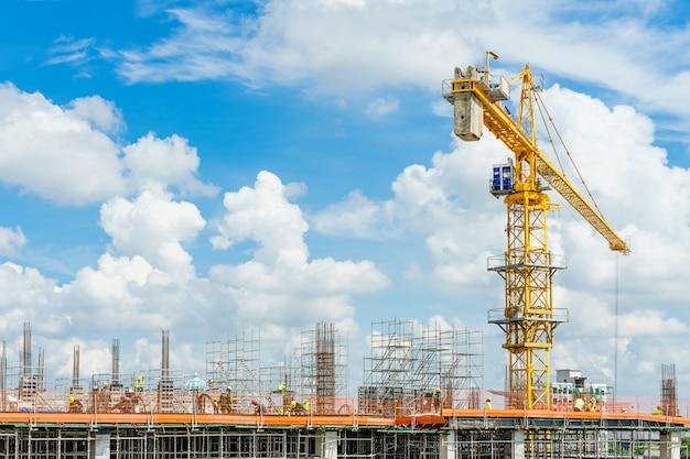 Bouwkranen en high-rise de bouw in aanbouw tegen blauwe hemel.