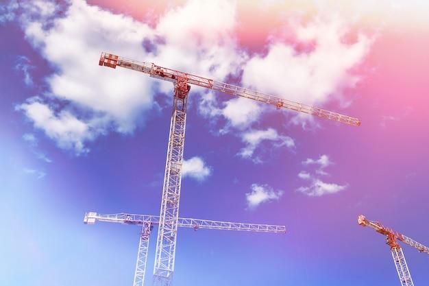 Bouwkranen werken op de scheppingsplaats tegen de blauwe hemelachtergrond. onderaanzicht van industriële kraan. concept bouw van flatgebouwen en renovatie van woningen. ruimte kopiëren