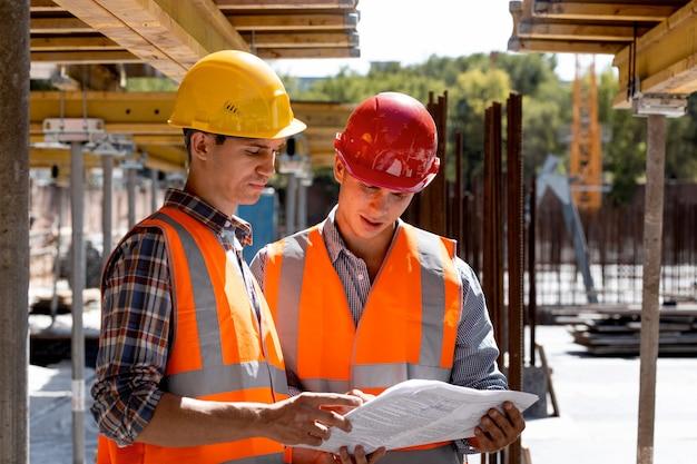 Bouwkundig ingenieur en architect gekleed in overhemden, oranje werkvesten en helmen verkennen bouwdocumentatie op de bouwplaats in de buurt van de houten bouwconstructies.