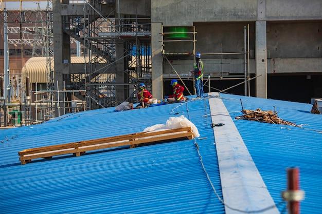 Bouwkundig ingenieur voorman staand dak voor werknemersteam om met hoge veiligheid te werken
