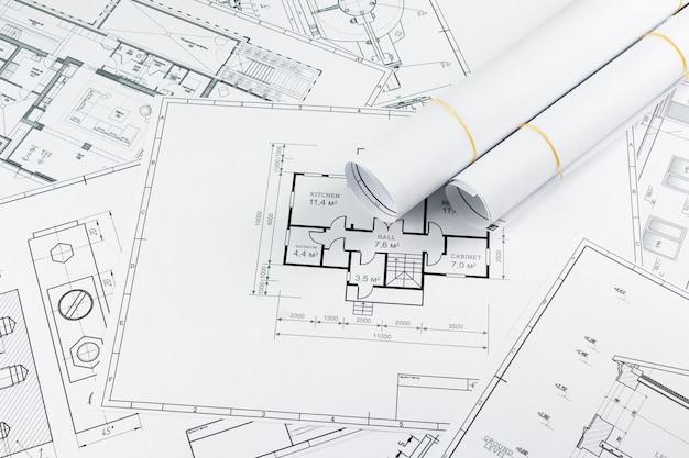 Bouwkundige constructietekeningen in een rol gedraaid, bouwprojecten op papier.