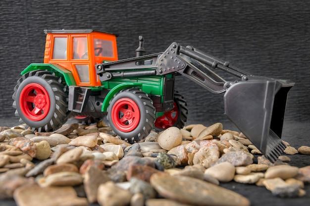 Bouwmachine voertuig, tractor speelgoed model over grind stenen