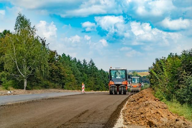 Bouwmachines voor wegenwerken passeren nieuw asfalt in de zomer van bomen