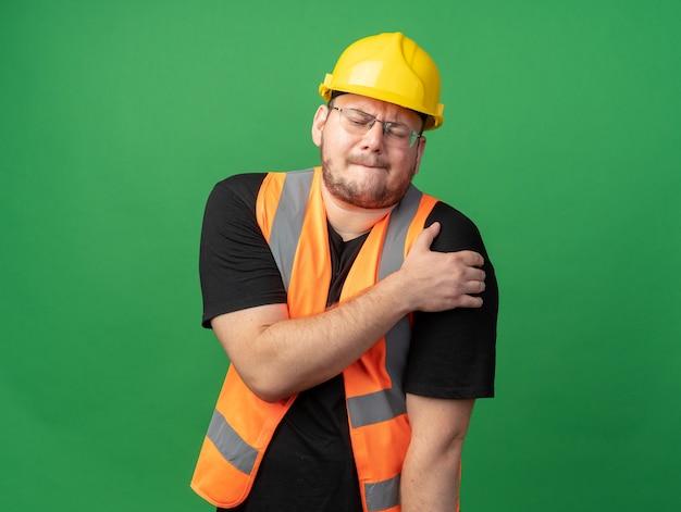 Bouwman in bouwvest en veiligheidshelm die er onwel uitziet en zijn schouder aanraakt, voelt pijn terwijl hij over groen staat