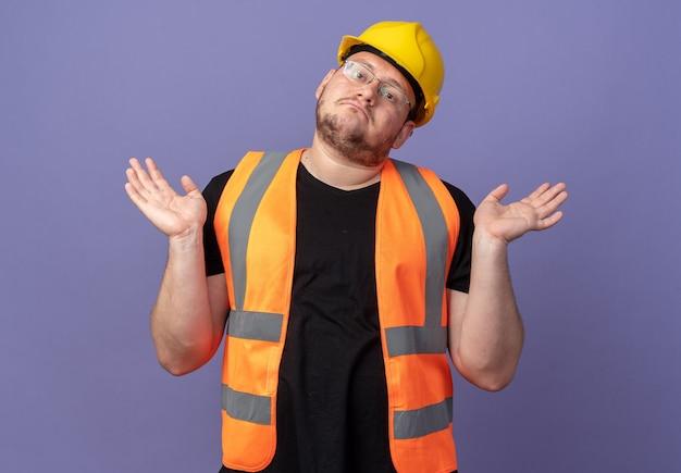Bouwman in bouwvest en veiligheidshelm kijkend naar camera verward schouders ophalend zonder antwoord over blauw