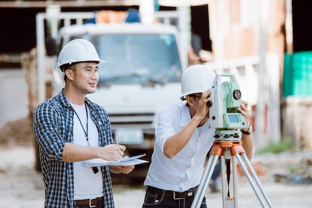 Bouwmanager en ingenieursteam dat plan op bouwplaats controleert. transportapparatuur voor theodolieten. ingenieur team. werken op de bouwplaats.