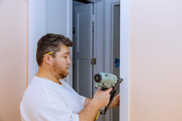 Bouwmanusje van alles die luchtspijkerkanon gebruiken die het binnendeurafgietsel van flat installeren