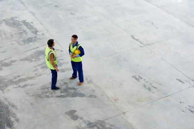 Bouwmedewerkers die bouw bespreken