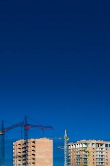 Bouwplaats. hoge gebouwen met meerdere verdiepingen in aanbouw. torenkranen bij gebouwen.