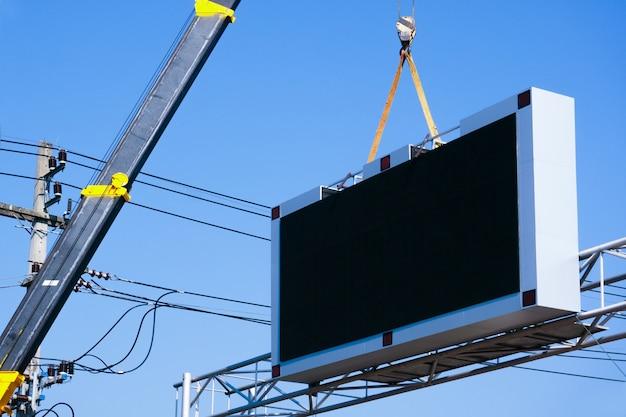 Bouwplaats kraan is een led bord opheffen leeg reclamebord op blauwe hemelachtergrond voor nieuwe advertentie