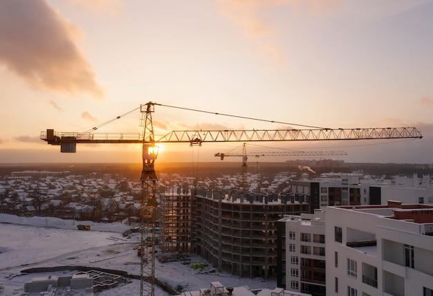 Bouwplaats met bouwkranen bij zonsondergang vanuit luchtfoto.