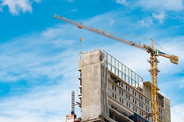 Bouwplaats met kraan en gebouw. onroerend goed industrie. de haspel van het kraangebruik heft apparatuur in bouwwerf op. gebouw van staal en beton. het kraanwerk tegen blauwe hemel en witte wolk